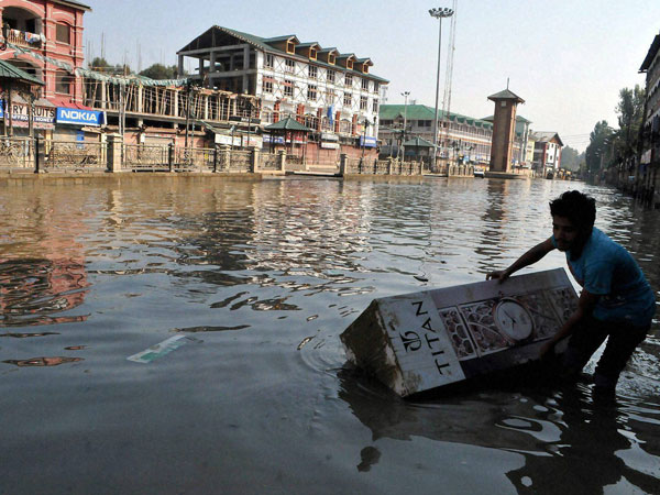 A shopkeeper tries to pull a submerged clock from the flooded road of the business hub of Lal Chowk in Srinagar