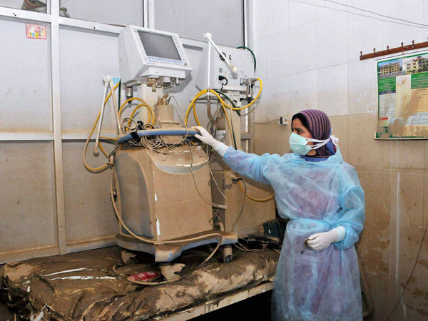 A hospital staff member looks at the damaged ventilator
