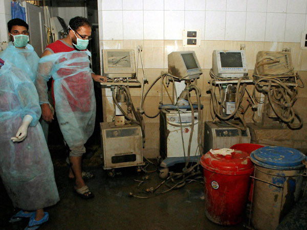 Hospital staff look at the damaged ventilators