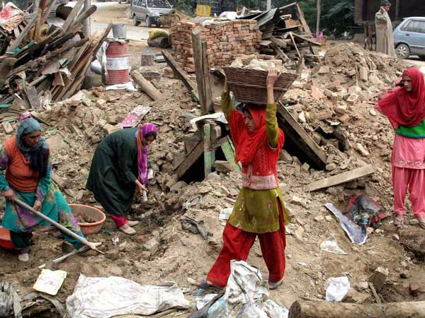 Women clearing the debris of a collapsed house