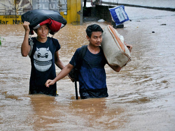 People wades through water logged street