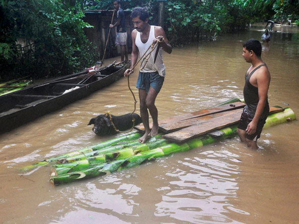 Villagers use a makeshift banana plantain raft to move across their flooded village