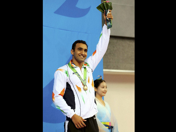 India's bronze medallist Sandeep Sejwal celebrates on the podium during medal ceremony for the men's 50-metre breaststroke swimming event at the 17th Asian Games in Incheon, South Korea on Friday.
