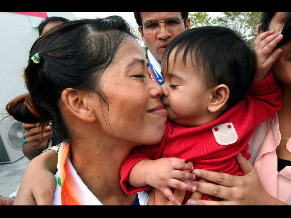 Indian boxer MC Mary Kom kisses her child after winning her round of 16 bout against Yeji Kim of Korea in Incheon on Saturday.