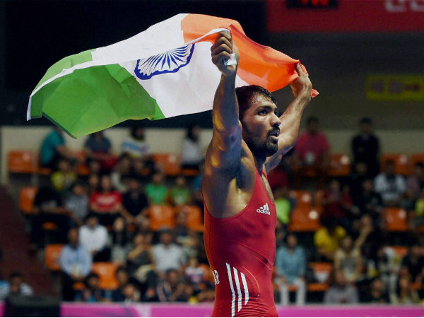 India's Yogeshwar Dutt celebrates with the tricolour after defeating Tajikistan's Zalimkhan Yusupov, winning gold medal in the men's 65 kg freestyle wrestling match at Dowon Gymnasium Stadium on Sunday.