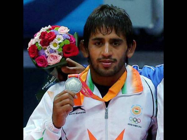 India's Bajrang Kumar poses with his silver medal in 61 kg freestyle wrestling match