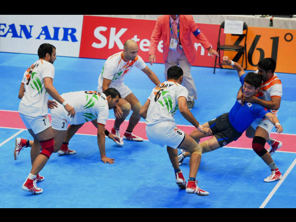 Indian players try to catch a Korean player (in blue) during the Men's Kabaddi semi-final match at the 17th Asian Games in Incheon on Thursday.