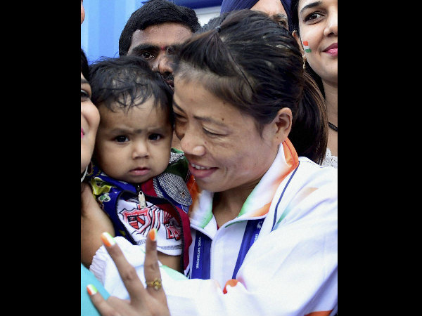 Mary Kom with her kid after winning the gold medal in women's flyweight (48-51kg) category at the Asian Games in Incheon on Wednesday.
