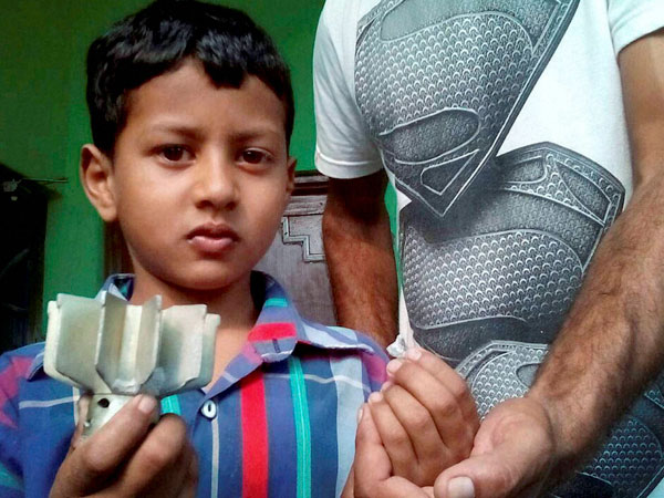 A boy shows a mortar shell following firing at village