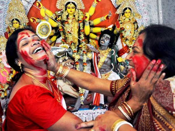 Married Hindu women playing with vermillon powder