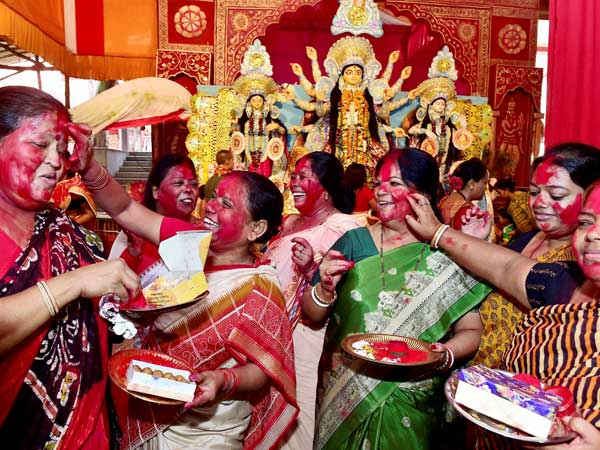Married Bengali women play with vermillon powder