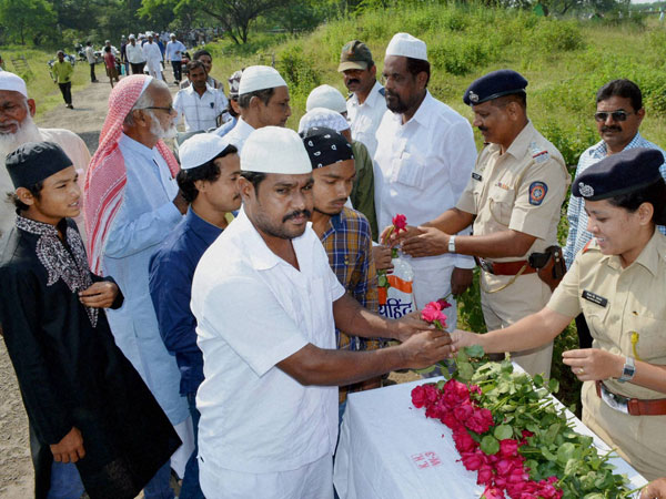 Police officers greet Muslims with roses