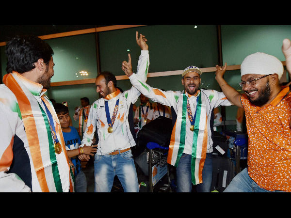 Players of the Asian Games gold medal winning Indian hockey team dance with their supporters upon arrival at IGI airport New Delhi on Sunday.