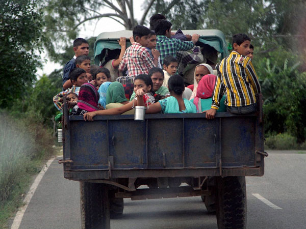 Children and women move to safer places on a tractor
