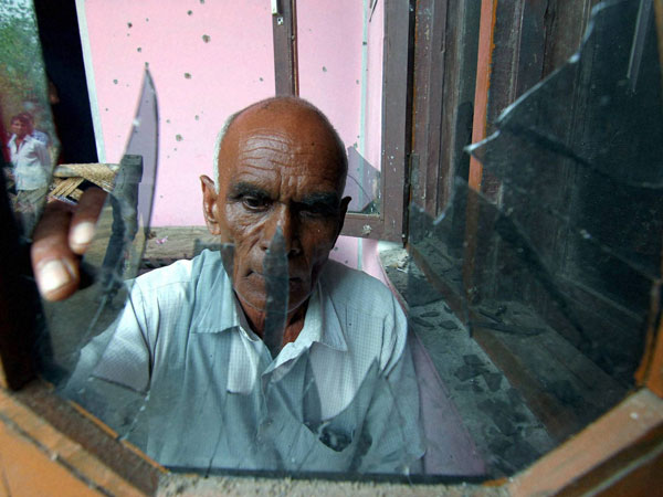 A man shows the broken glass pane of his house