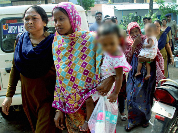 A police woman escorts two women with their children, accused in Burdwan blast, on the way to CID headquarters in Kolkata, in Burdwan on Wednesday.