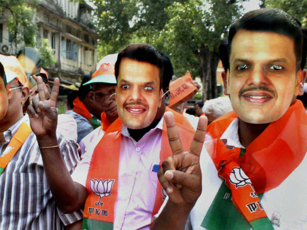 BJP workers wear mask of Maharashtra BJP president Devendra Fadnavis while celebrating the party's victory in Assembly polls in Nagpur, Maharsahtra on Sunday.