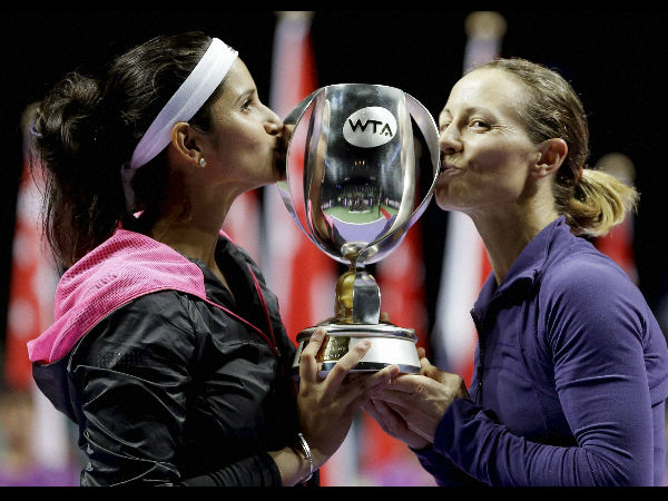 Sania Mirza and Cara Black kiss the trophy after their win at the WTA Tour finals.