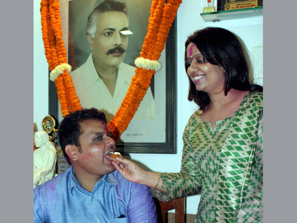 Devendra Fadnavis being offered sweets by his wife Amruta