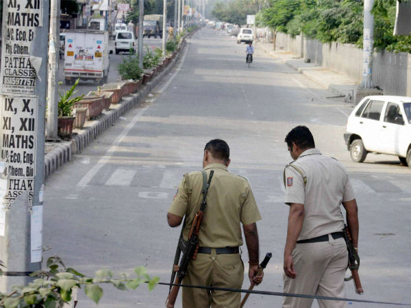 New Delhi: Police men walk in a street during curfew in violence-hit Trilokpuri in New Delhi on Monday. (PTI Photo)