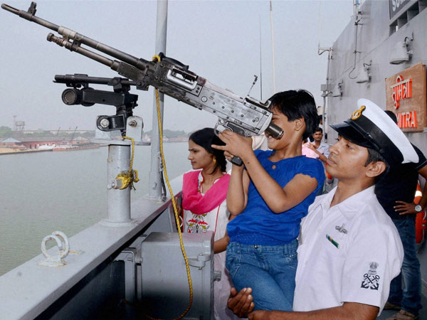 A naval officer helps a school girl to have a look