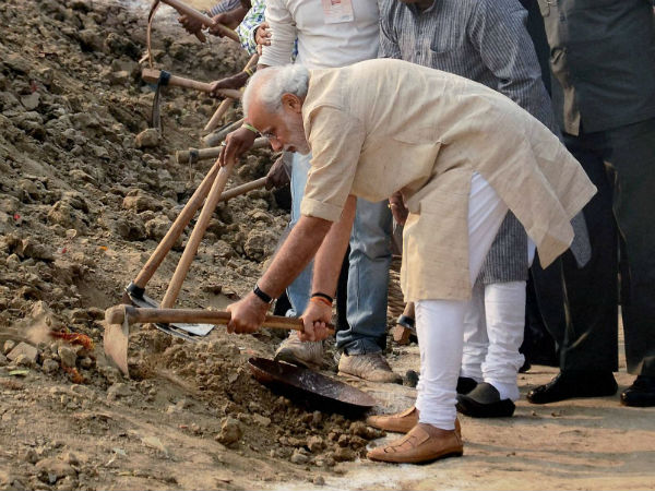 Varanasi: Prime Minister Narendra Modi wields a spade as he participates in the 'Swachh Bharat Campaign' at Assi Ghat in Varanasi on Saturday. (PTI Photo)