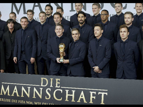 The players of the German national soccer team pose with the World Cup trophy as they arrive for the premiere of the movie 'Die Mannschaft' (The Team) in Berlin, Germany, Monday, November 10, 2014.