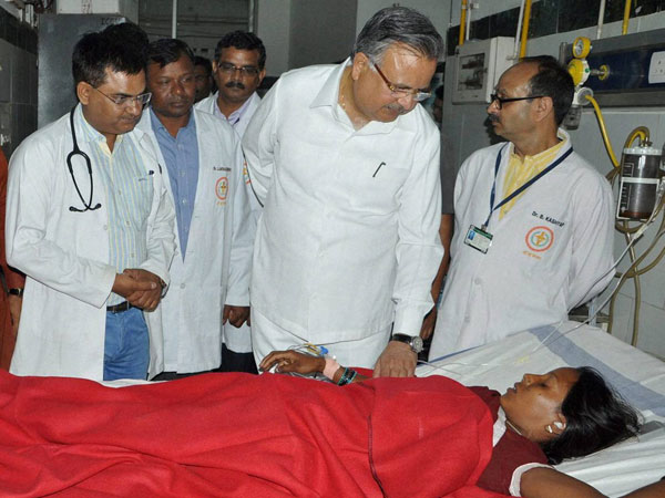 Chhattisgarh Chief Minister Raman Singh meets a woman who underwent sterilization surgeries receive treatment at the CIMS hospital in Bilaspur, Chhattisgarh on Tuesday.