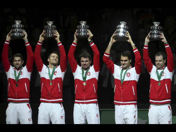 Swiss team, from the left, Michael Lammer, Marco Chiudinelli, Stanislas Wawrinka, Roger Federer and coach Severin Luthi hold their trophy after winning the Davis Cup final at the Pierre Mauroy stadium in Lille, northern France, Sunday