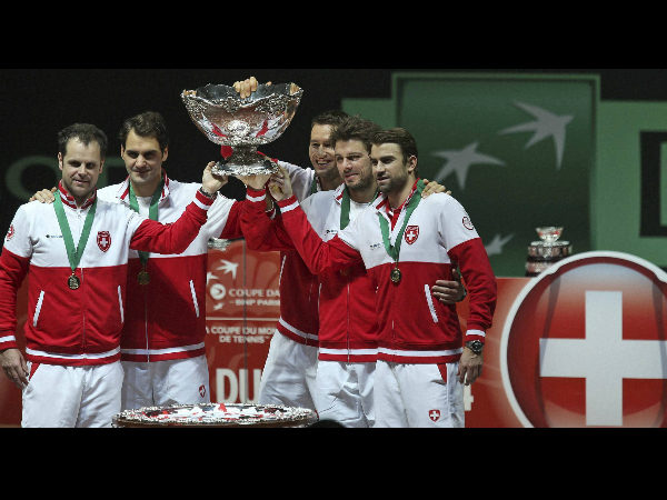 Team Switzerland with coach Severin Luthi, left, Roger Federer, second left, and Stanislas Wawrinka, second right, hold the trophy after winning the Davis Cup final