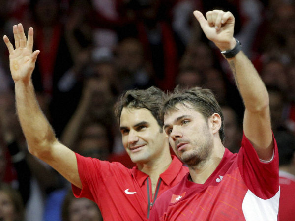 Federer, left, and compatriot Stanislas Wawrinka, right wave after defeating French pair Julien Benneteau and Richard Gasquet