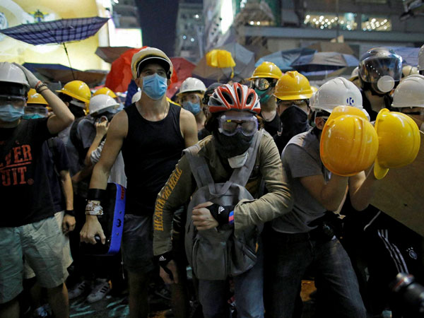 Protesters prepare to push against policemen at an occupied area