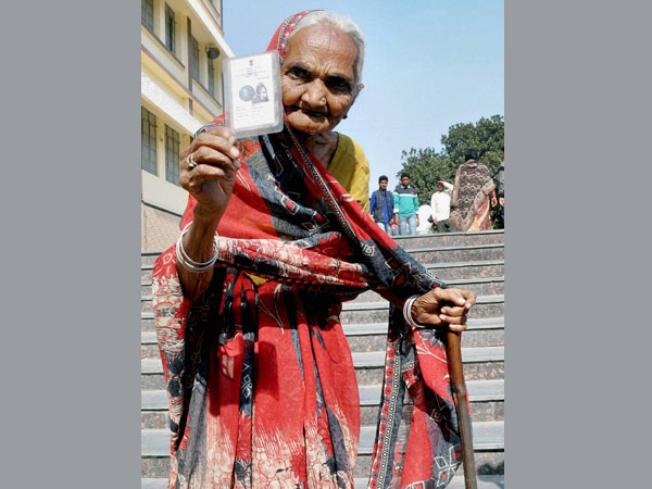 An elderly woman shows her voter card