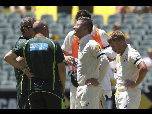 Clarke, second from right, grimaces in pain after injuring himself