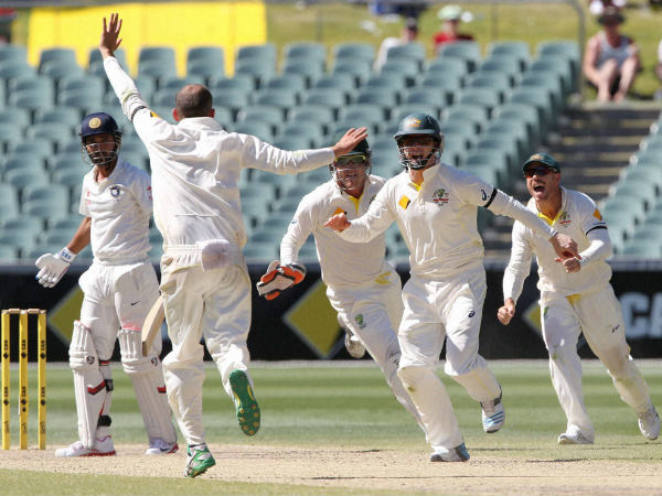Chris Rogers celebrates with teammate Nathan Lyon, second left, after catching out Ajinkya Rahane