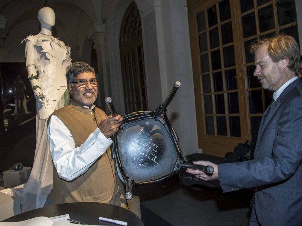 Nobel Peace Prize laureate 2014, Kailash Satyarthi, left, shows what he scribbled under a chair at the Nobel Museum in Stockholm, Sweden.