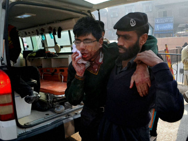 A hospital security guard helps a student injured in the shootout at a school under attack by Taliban gunmen in Peshawar.