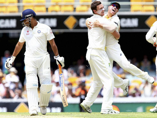Josh Hazlewood, centre, celebrates with David Warner after getting the wicket of Dhoni