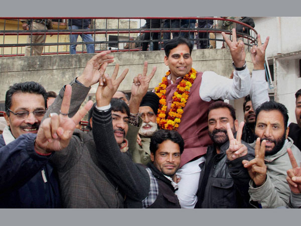 BJP candidate Gagan Bhagat with his supporters flash victory sign after won from R S Pura constituency in Jammu on Tuesday.