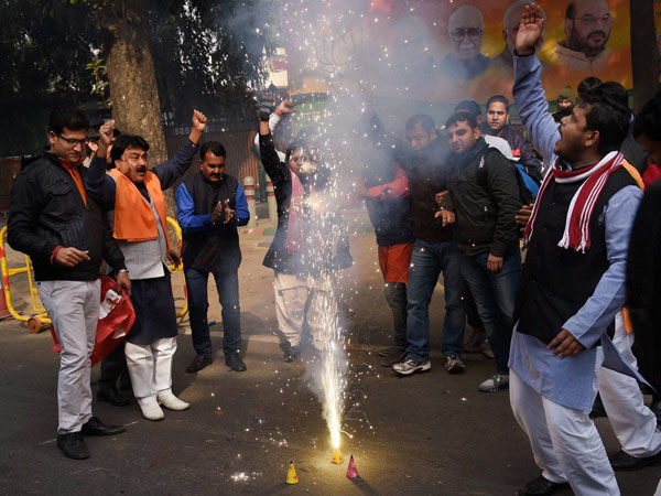 BJP supporters burst crackers as they celebrate party's victory in J&K and Jharkhand Assembly polls, at BJP headquarters in New Delhi on Tuesday