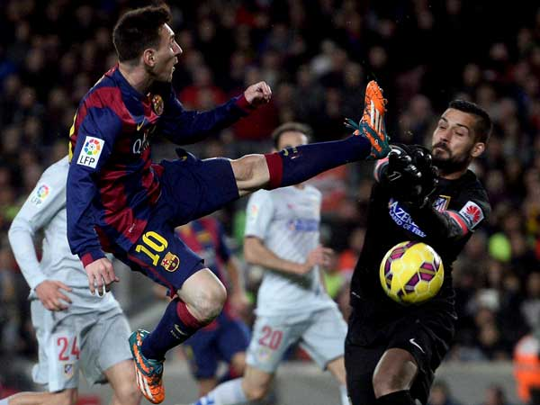 Barcelona's Lionel Messi (left), duels for the ball against Atletico Madrid's goalkeeper Miguel Angel Moya during the Spanish La Liga soccer match between FC Barcelona and Atletico Madrid