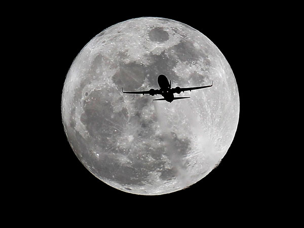 A commercial airliner crosses the first full Moon of the year