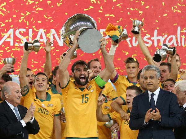 Australian football team celebrate with their trophy