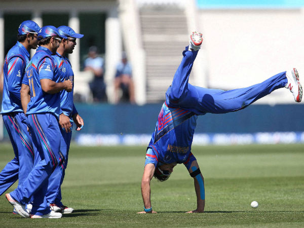 Afghanistan's Hamid Hassan is watched by his teammates as he performs a hand-stand after taking a catch to dismiss Scotland's Josh Davey during their World Cup match
