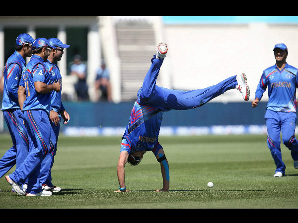 Afghanistan's Hamid Hassan is watched by his teammates as he performs a hand-stand after taking a catch to dismiss Scotland's Josh Davey during their Cricket World Cup Pool A match
