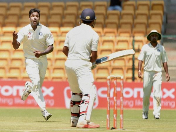 Varun Aaron (left) celebrates the wicket of Karnataka's Mayank Agarwal (centre)