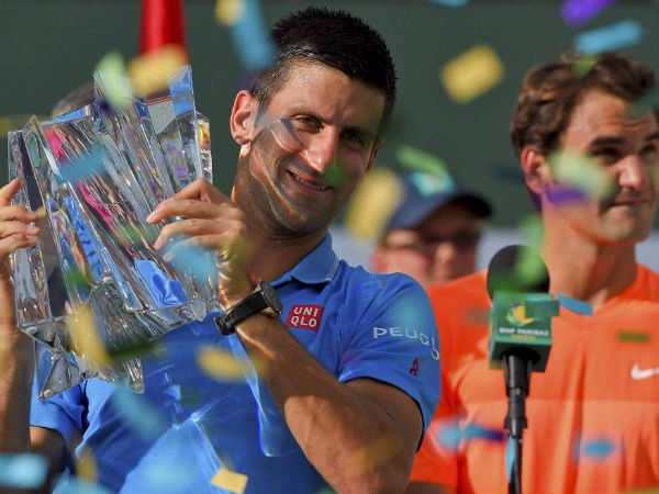 Novak Djokovic (left) poses with the trophy in front of Roger Federer of Switzerland at Indian Wells