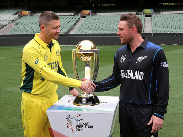 Clarke (left) shakes handes with NZ captain Brendon McCullum after posing in front of World Cup trophy on Saturday