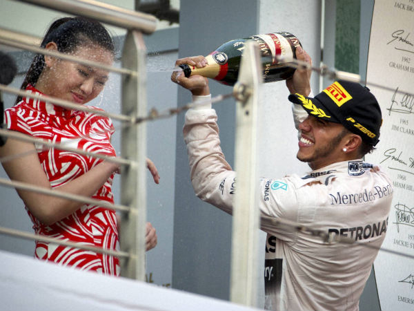 Mercedes driver Lewis Hamilton of Britain sprays champagne on a track attendant on the podium after winning the Chinese Formula One Grand Prix at Shanghai International Circuit in Shanghai
