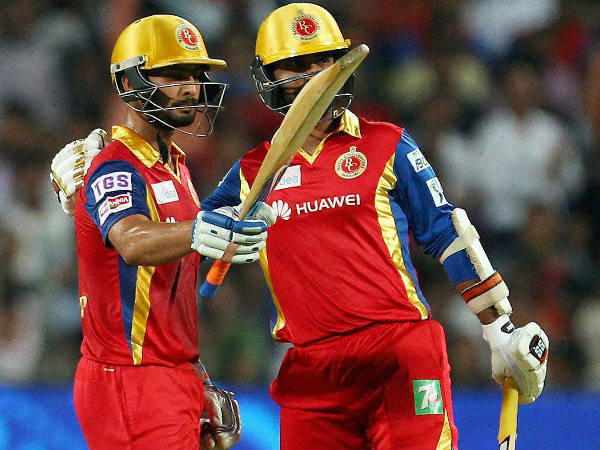 Mandeep (left) celebrates his half century as Dinesh Karthik looks on